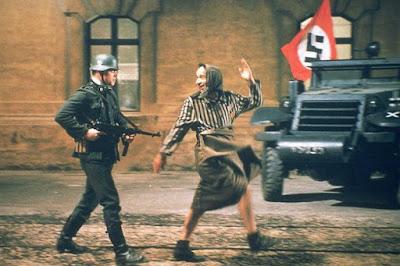 Fotograma de la película La vida es bella que muestra  a su protagonista, Guido (R. Benigni), danzando de forma muy cómico seguido de un soldado nazi que le apunta con un fusil