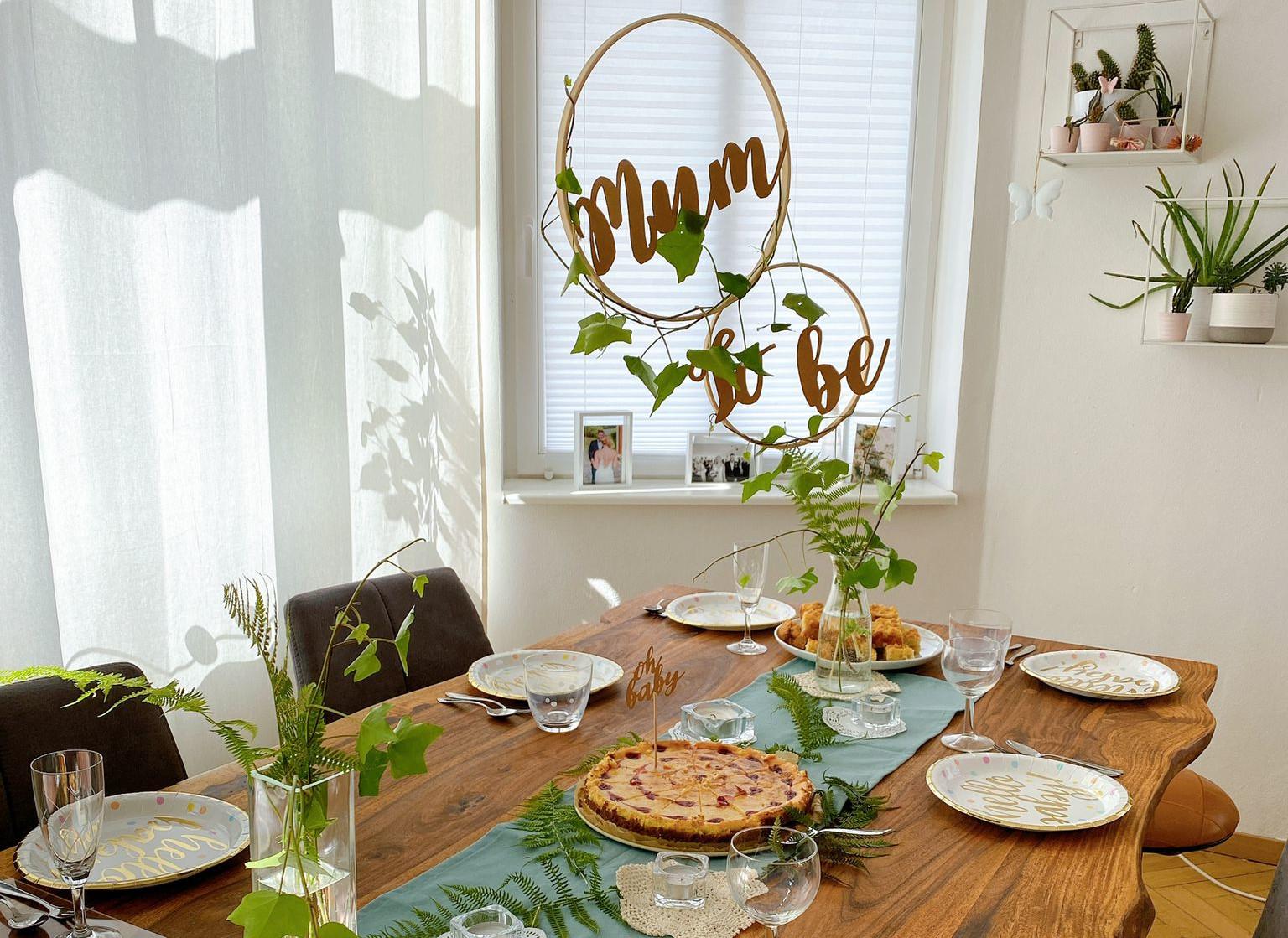 Dekoration einer Babyparty - ein gedeckter Tisch mit Grün