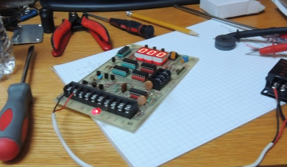 "Main circuit board on a desk showing score of ""000"" and surrounded by tools"