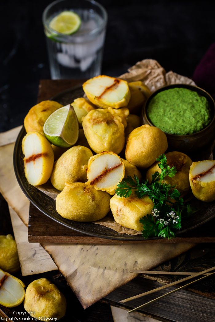 These mini kenyan style stuffed baby potatoes are served on a black plate with green chutney.