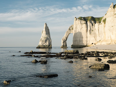 White cliffs on a beach with white spyres coming out of the light blue sea. Normandy, France