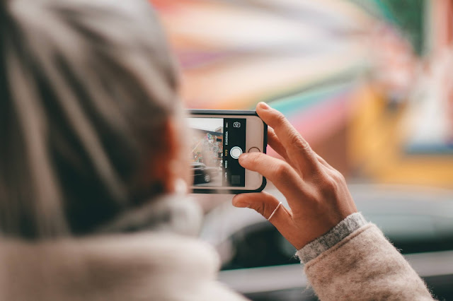 A woman taking a photo on a mobile phone
