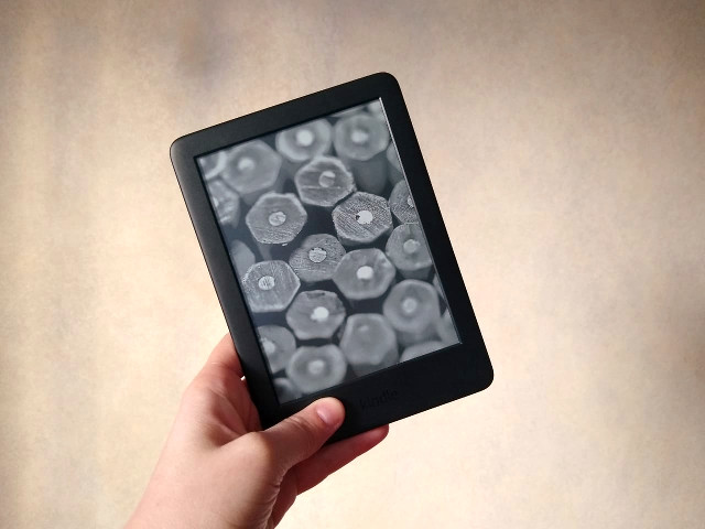 A hand holding a Kindle with an beige background.