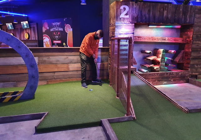 Playing hole 1 of the Crazier Golf course at Boom: Battle Bar at the Castle Quarter shopping and entertainment centre in Norwich