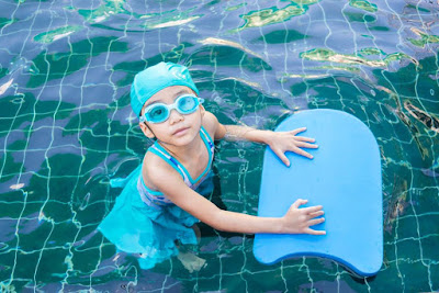 picture of a child in a pool, holding a kickboard looking at the person taking the photo. Children can have different learning styles for swimming. Some are visual learners.