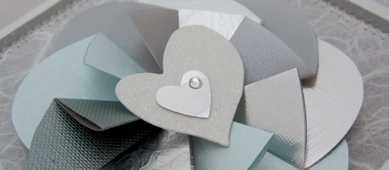 Silver colored paper folded flower for handmade card