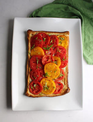 tomato and ricotta tart with puff pastry crust on white rectangle platters with basil on top