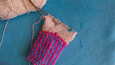 a white mitten-in-progress with a two-colour ribbed cuff in blue and pink.