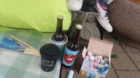 """close up: Decke, mit zwei Bierflaschen, auf der einen steht """"Kellerkind"""", Fächer, daneben meine Schuhe und Straßenmalkreide, sowie mein Kaffeebecher"""