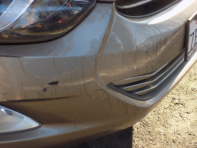 Scratched bumper before collision repairs at Almost Everything Auto Body.