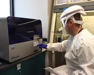 Capt. Nicholas Buck uses a lab device in full protective gear