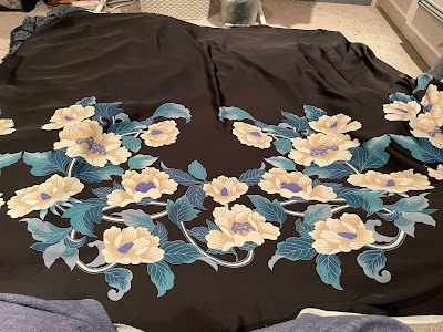 a piece of black fabric with an extremely large cream and teal floral border print