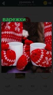 изящные варежки красного цвета с узорами, в руках чашки белого цвета