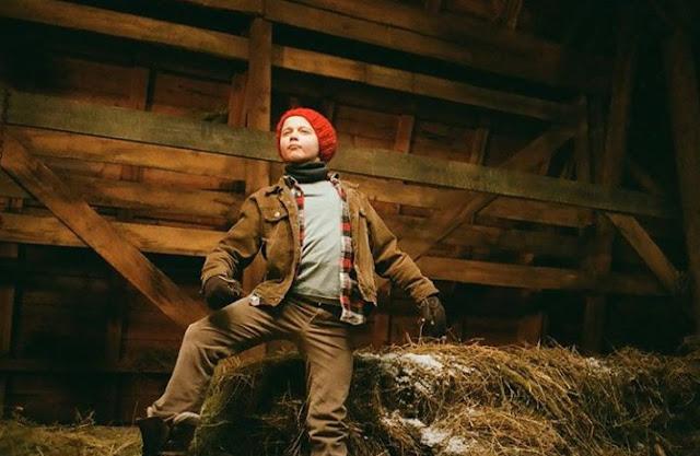 El actor sordo Danny Murphy en un pajar con gorro rojo, cazadora y pantalón marrones