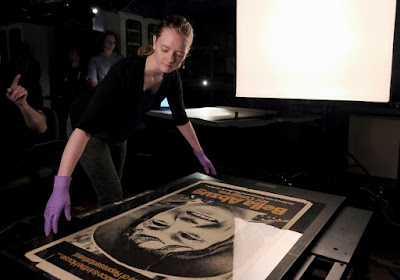 Amelia Brookins, object handler, arranges a poster of Bella Abzug to be photographed at the Smithsonian National Museum of American History.