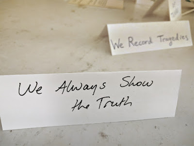 "An example of a Value, ""We Always Show the Truth"" with one in the background reading ""We Record Tragedies."""