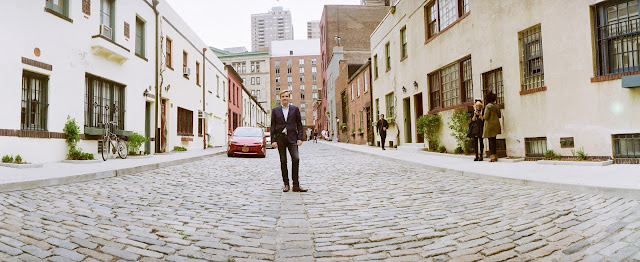 Ted wears a dapper blue suit on the cobblestone street in the West Village