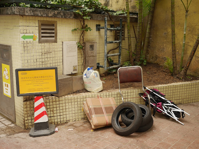 broken seat, worn tires, and broken baby stroller at trash collection point in Macau
