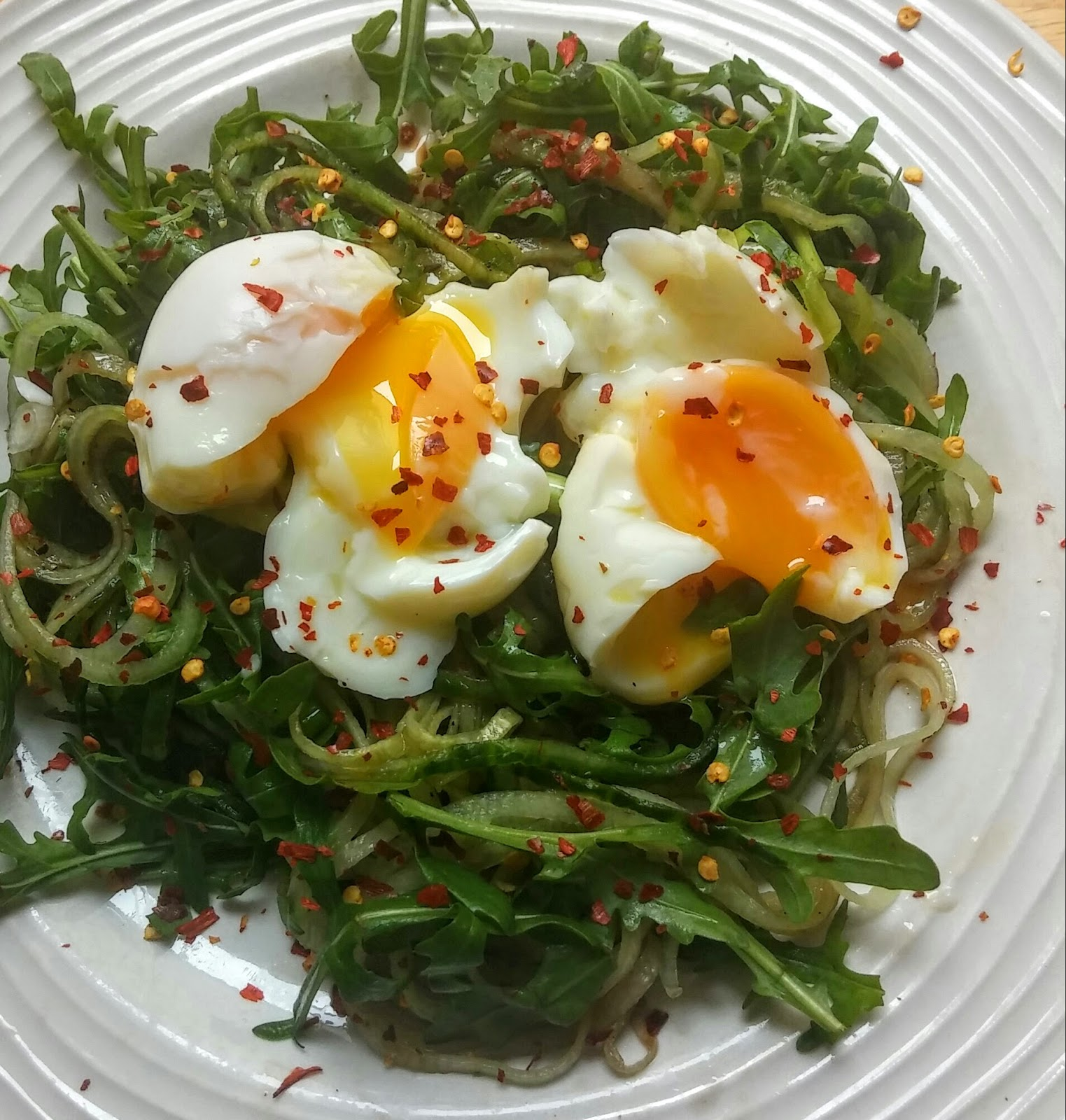 Perfectly cooked boiled eggs with runny yolks on a bed of spiralized cucumber combined with rocket in a hot and sour dressing