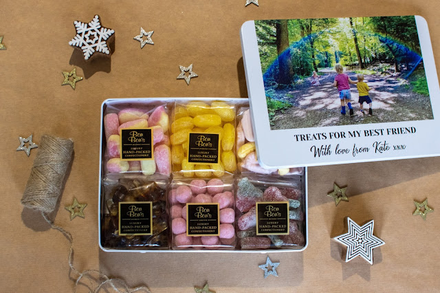 """A white aluminium tin with a photograph on the front and a message """"to my best friend, lots of love Kate xxx"""" . The tin is open to show 6 packets of sweets. It came from Proper Goose and has been personalised as a gift"""