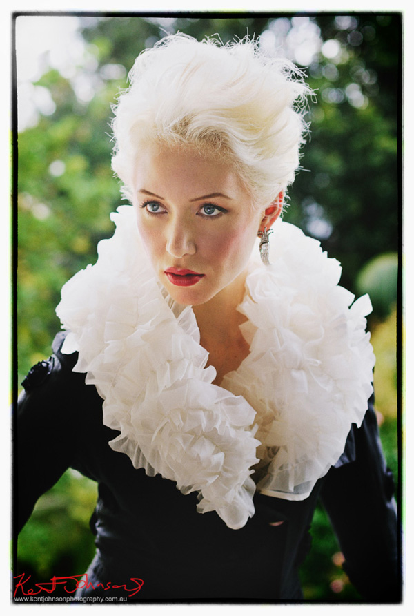 Heritage house location fashion photoshoot. Classic beauty, model with short platinum hair in black silk jacket with wide white ruffle collar. Photographed by Kent Johnson, Sydney, Australia.