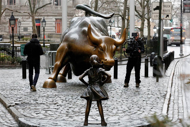 Statue of girl placed in front of iconic charging Wall Street bull