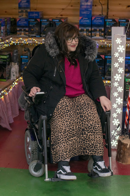 Woman sat in powerchair wearing leopard print maxi skirt, Vans trainers, pink jumper and black parka coat. Christmas lights behind her