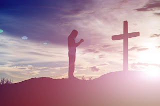 A person praying in front of a cross