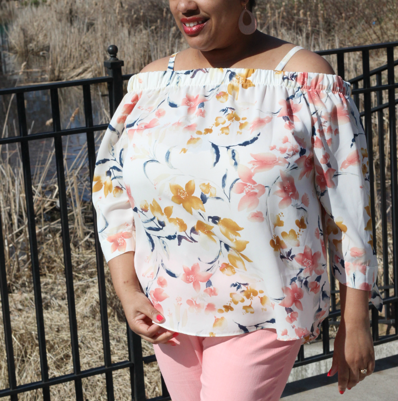 a woman wearing a floral blouse and pink jeans