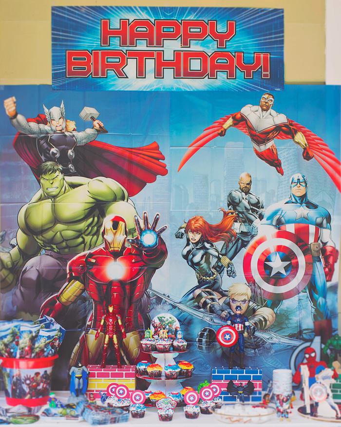 Decorated Avengers superhero birthday party backdrop and dessert table