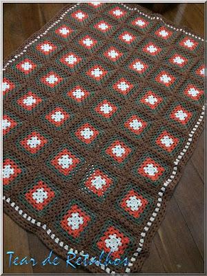 """Visão geral de uma manta de crochê para sofá feita com a técnica dos """"quadradinhos da vovó""""."""