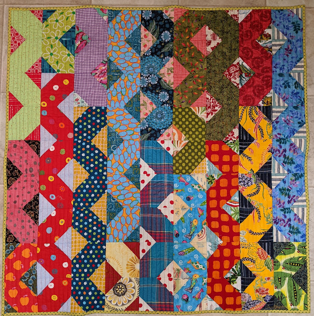Hatchet blocks form ribbons of color down a quilt
