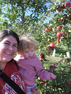 a woman with dark hair holds a fair haired toddler in front of an apple tree