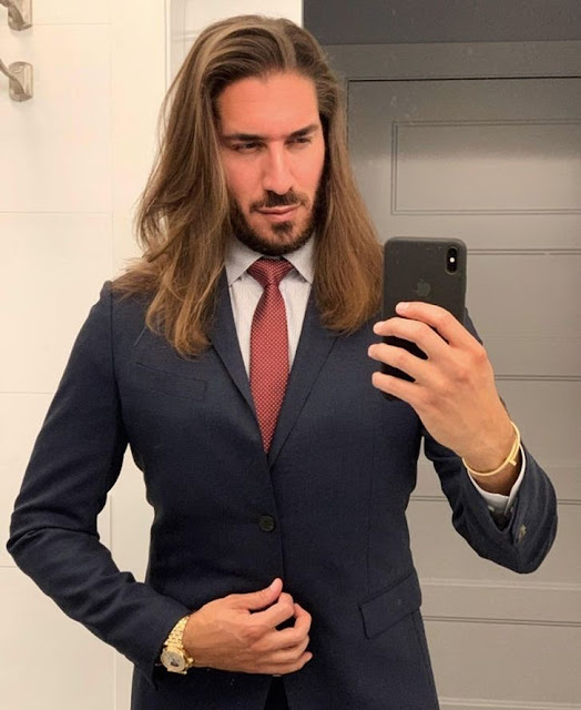 How unexpected - long curls and a formal suit