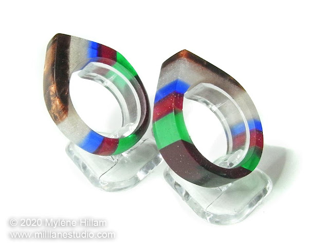 Two multicoloured striped resin rings shaped to a point