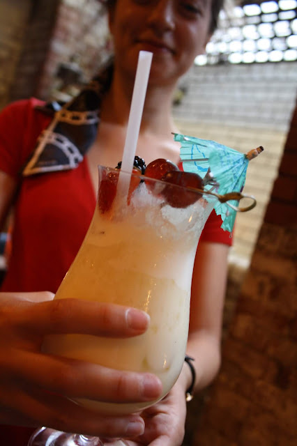 The photo focuses on a Pina colada cocktail, held up to the camera by Abbey. She is visible in the background, although out of focus