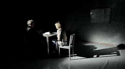 Imagen de una mujer en una habitación en penumbra siendo interrogada