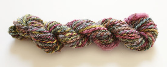 A 2-ply skein of yarn hand spun with rainbow-dyed wool on a white background.