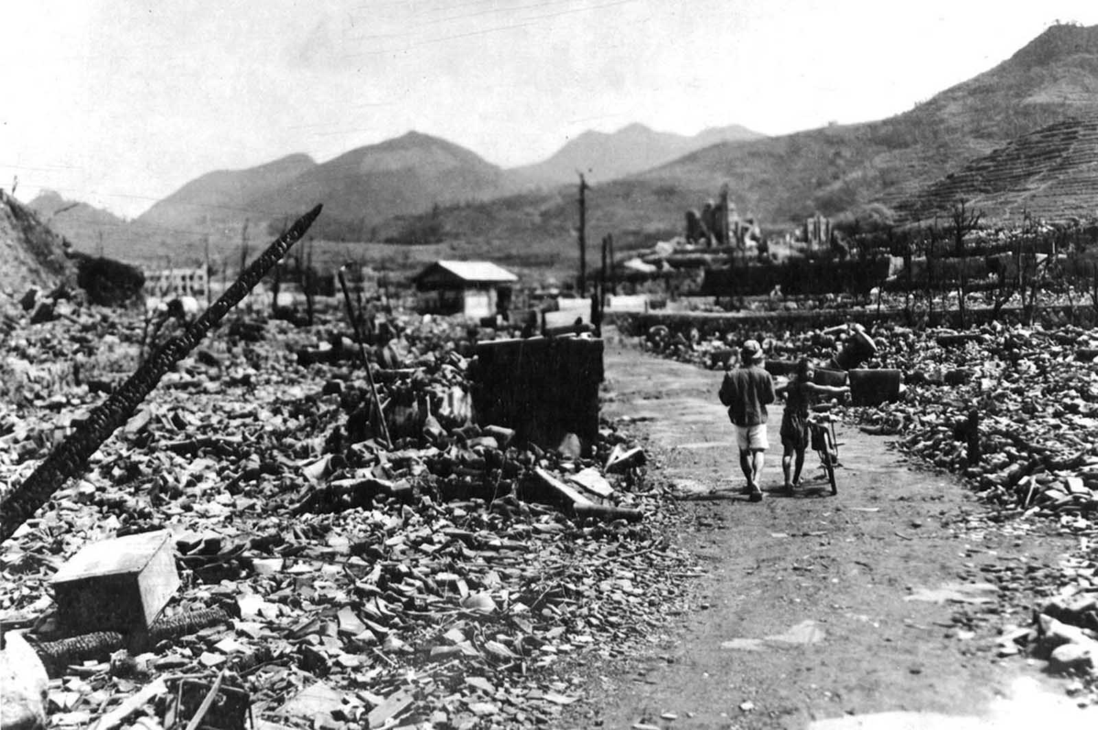 People walk through the charred ruins of Nagasaki, shortly after an atomic bomb destroyed much of the city. The explosion generated heat estimated at 3,900 degrees Celsius (4,200 K, 7,000 °F).