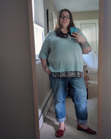 image of me standing in a full-length mirror, wearing a light aquamarine top with a red and white floral pattern on the bottom and back, blue jeans, and red loafers