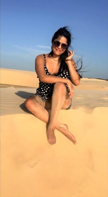 mulher sentada em uma duna de areia