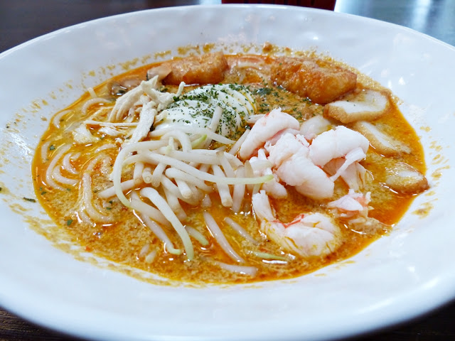 Traditional Singapore laksa, spicy noodle soup with prawns, cockles, chicken and fish cake