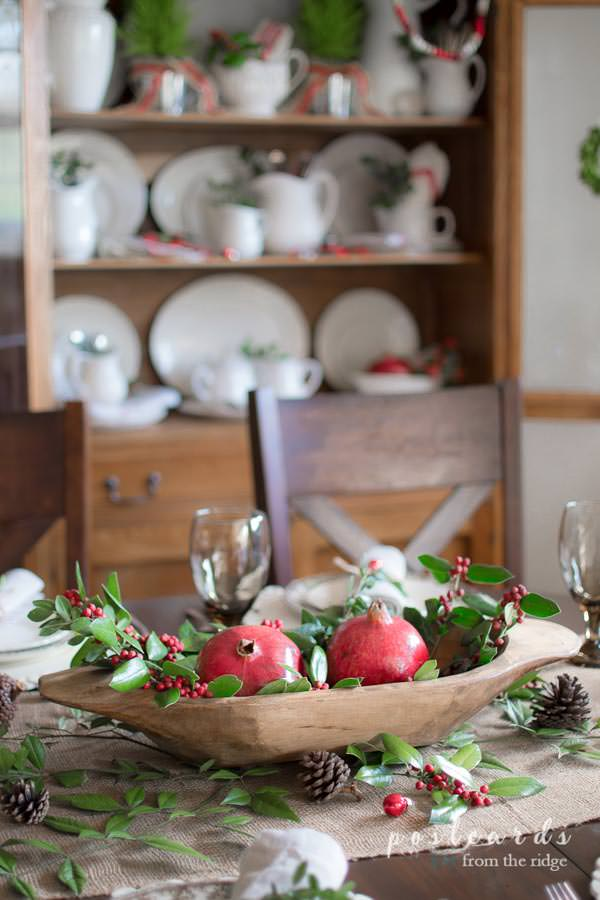 wooden bowl with pomegranates and holly branches as Christmas table centerpiece