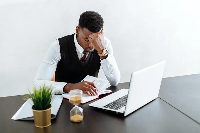 Hombre sentado sobre un escritorio frente a una computadora