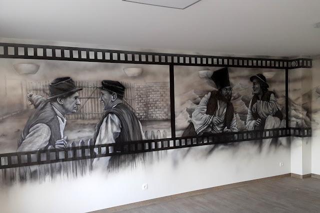 Malowanie obrazu na ścianie w pokoju telewizyjnym, artystyczne malowanie ściany w motyw z filmu Janosik, grafika w sali telewizyjnej