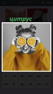 девушка в желтой кофте закрыла глаза желтыми половинками лимона