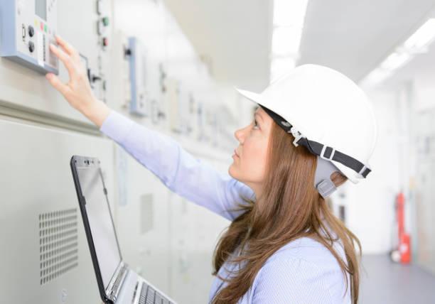 Seorang teknisi perempuan sedang membetulkan mesin dan listrik