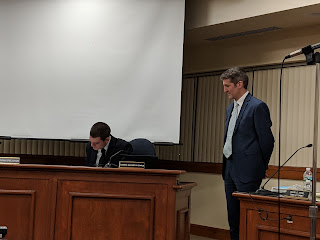 new TA Jamie Hellen waits for Councilor Earls to be the last to sign the contract before signing it himself