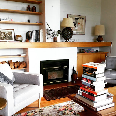Large stack of second-hand books on a coffee table in a mid-century modern living room.