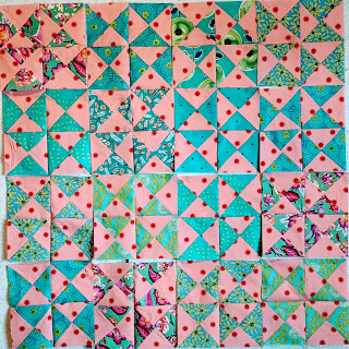Sixteen sets of four hourglass blocks with different turquoise print fabrics combine with pink with red polka dot fabric/